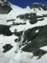 Waterfall below Train Glacier emerging from beneath the snow and disappearing back beneath the snow.