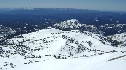 View of Lassen's south slopes from summit. Note party of skiers near bottom left and plowing progress at center-right.